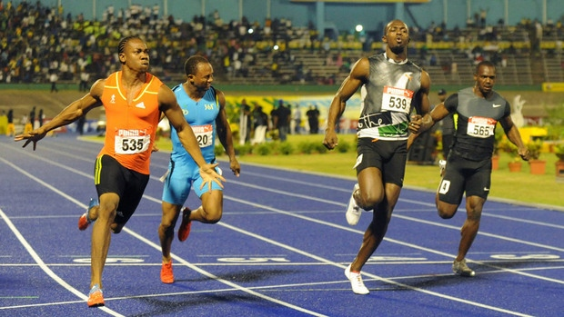 Yohan Blake, left, celebrates after crossing the finish line ahead of current world-record holder Usain Bolt, second from right, to win the 100m final at Jamaica's National Championships in Kingston, in 2012. (Collin Reid/Associated Press)