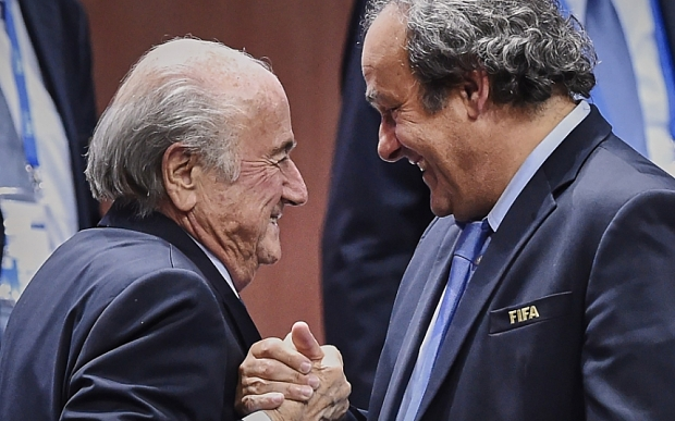 (FILES)-- A file photo taken on May 29, 2015 shows FIFA President Sepp Blatter (L) shaking hands with UEFA President Michel Platini after being re-elected following a vote to decide on the FIFA presidency in Zurich. UEFA chief Michel Platini revealed in a letter sent on September 28, 2015 to 54 European UEFA federations, that a payment made to him from Blatter had been