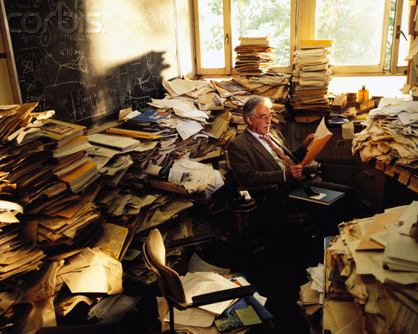 "Original caption: One of the leading theoretical physicists of CERN, retired Professor Dick works in his office. Despite the look of his office, he is still the master of his universe. His individual stacking order is world famous since he only needs a maximum of 5 seconds to find ANY paper in his office. Many colleagues used his ""filing"" method to shortcut their own search for publications. --- Image by © Peter Ginter/Science Faction/Corbis"