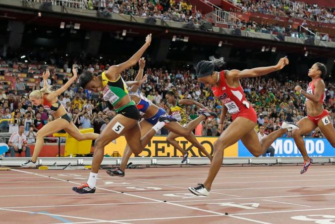 Jamaica's Danielle Williams, with number 5, crosses the finish line to win the women's 100m hurdles final at the World Athletics Championships at the Bird's Nest stadium in Beijing, Friday, Aug. 28, 2015. (AP Photo/David J. Phillip)