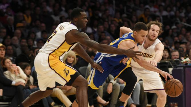Golden State Warriors guard Stephen Curry, center, moves the ball while Los Angeles Lakers forward Brandon Bass, left, and guard Marcelo Huertas, right, defend during the second half of an NBA basketball game in Los Angeles, Sunday, March 6, 2016. The Los Angeles Lakers won 112-95. (AP Photo/Kelvin Kuo)