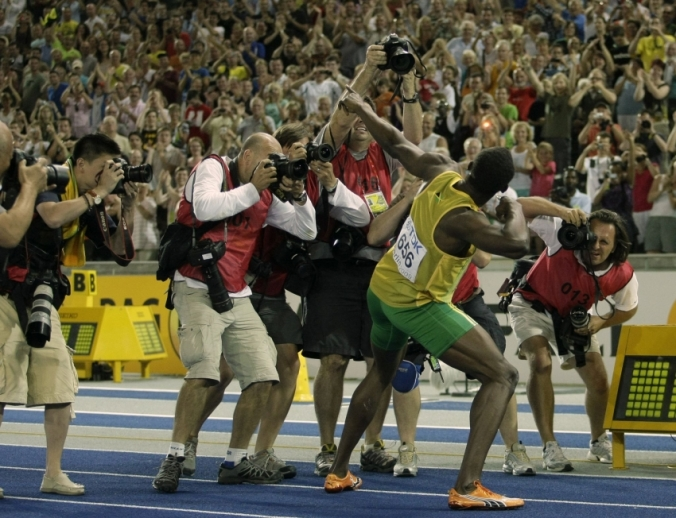 Usain Bolt celebrates with his signature pose after setting a world record in the 100m at the Berlin World Championships.