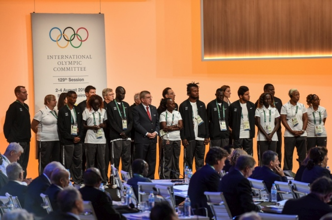 The Refugee Olympic Team takes to the stage with IOC President Thomas Bach to be introduced to all members of the International Olympic Committee. © UNHCR/Benjamin Loyseau