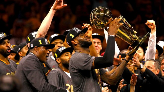 LeBron James hoists the Larry O'Brien NBA Championship Trophy after the Cleveland Cavaliers come from 3-1 down in the series to defeat the Golden State Warriors in the 2016 NBA Finals. (Photo credit: Ezra Shaw)
