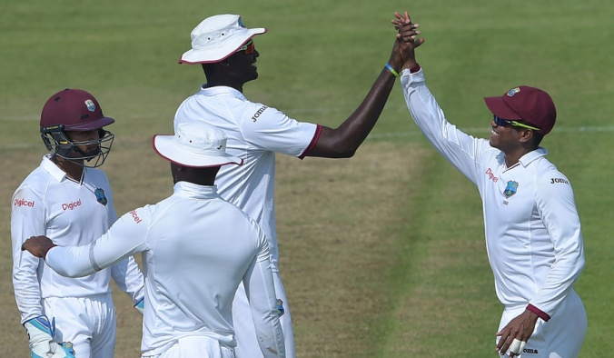 West Indies' cricket captain Jason Holder (C) celebrates with teammate Leon Johnson (R) after the dismissal of Pakistani batsman Younis Khan (unseen) on the first day of the third and final Test between Pakistan and West Indies at the Sharjah Cricket Stadium in Sharjah on October 30, 2016. Pakistan captain Misbah-ul-Haq won the toss and opted to bat against West Indies in the third and final Test in Sharjah. / AFP / AAMIR QURESHI (Photo credit should read AAMIR QURESHI/AFP/Getty Images)