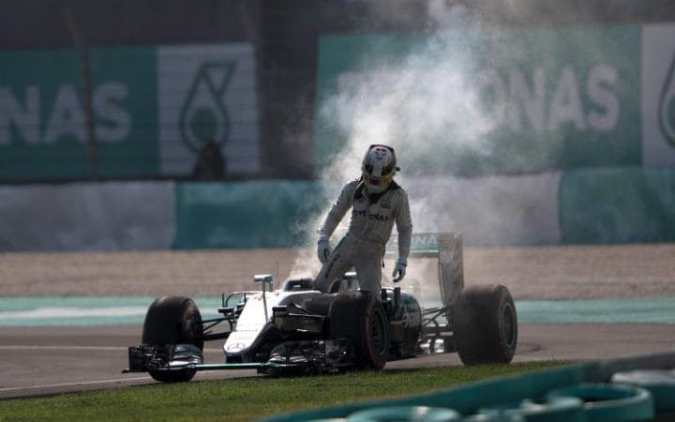 Disaster for Hamilton as he climbs out of his car after engine failure. Rosberg finished third behind Red Bull one-two. (Photo credit: AP)