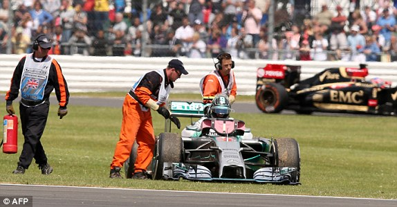 Lewis Hamilton wins as Nico Rosberg climbs out of his car after retiring from the British grand prix at Silverstone (Photo credit: AFP)