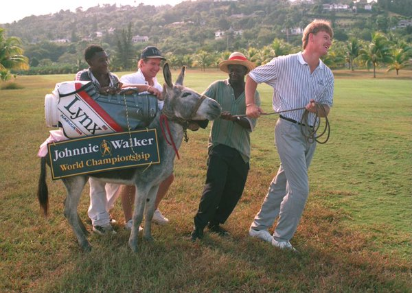 Ernie Els (right) is seen pulling a donkey across the Tryall Golf Course at the 1994 Johnnie Walker World Golf Championship. (Photo credit: Unknown)