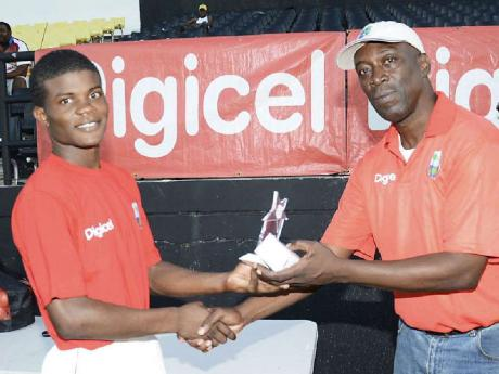 Philip Service handing over an award to Nicholas Walters at a Grassroots Cricket Fun Day (Contributed)
